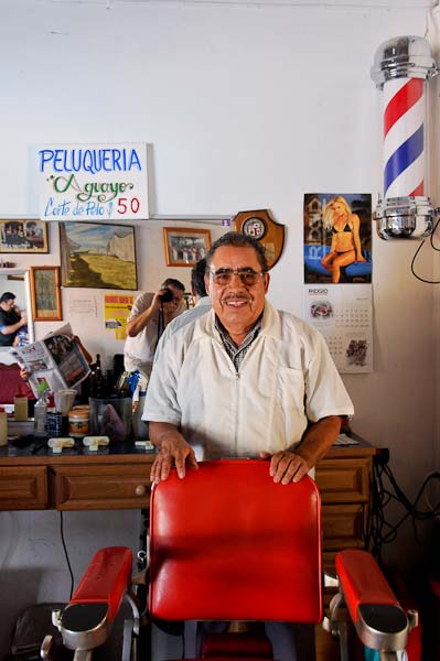A friendly barber.  Note the barber pole and, if you look closely, the photographer in the background.
