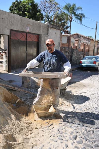 Sifting sand through a hand sieve.  Most of the labor is done by hand and is back-breaking work.